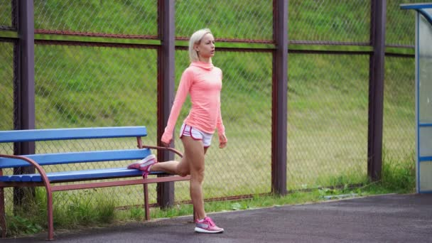 Adult fitness woman doing lunges with a jump on a sports ground