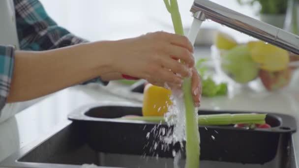 mladá žena mytí zeleniny