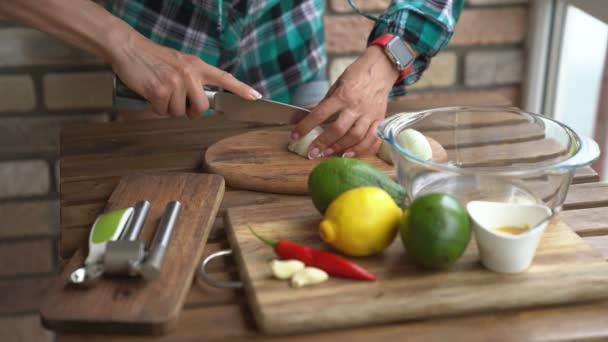 Žena řezání cibule a guacamole recept v kuchyni