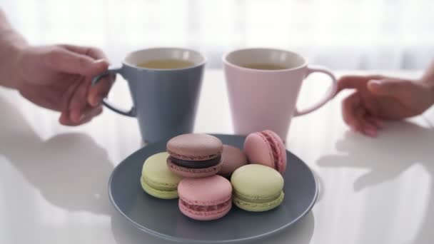 Close up of male and female hands holding cups of coffee with macaroons are on table