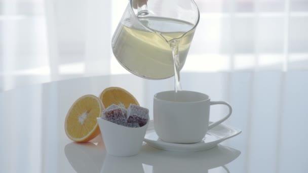 Detail hrnek čaje a marmelády na bílém stole. Žena nalévá čaj