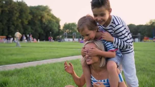 Family lifestyle scene of mother and sons resting together on green grass in the park.