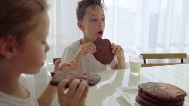 Two boy eating homemade chocolate cookies with milk at kitchen