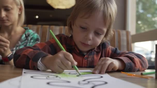 Child draws with crayons on a piece of paper in cafe. Preschool education