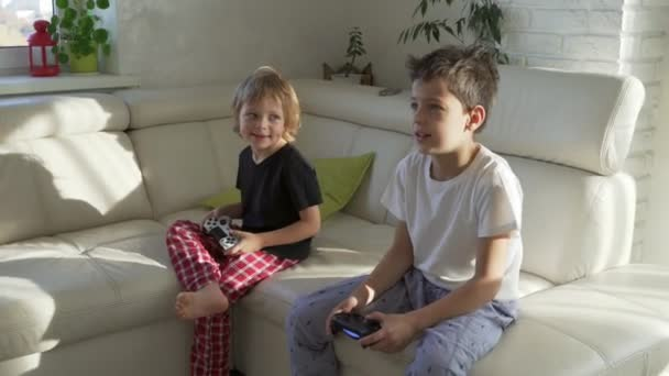 Two kids emotionally playing videogames at home at sunny morning