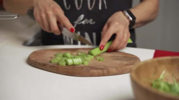 woman cuts celery on a cutting Board for cooking homemade vegetable salad