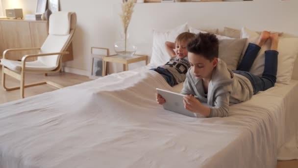 Dvě kavkazské děti, chlapec bratři hrají doma v posteli na tabletu.