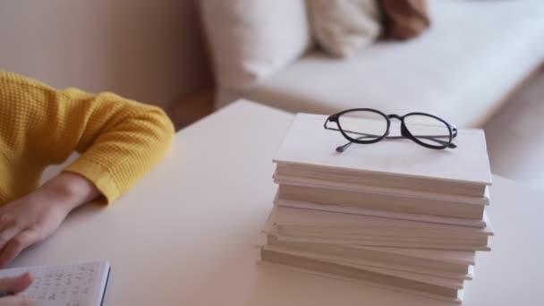 Fiú iskolai házi feladatot, írja egy golyóstoll a notebook.