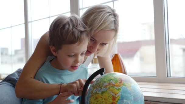 An attractive mother of caucasian ethnicity uses a globe to show her young son the countries of the world.