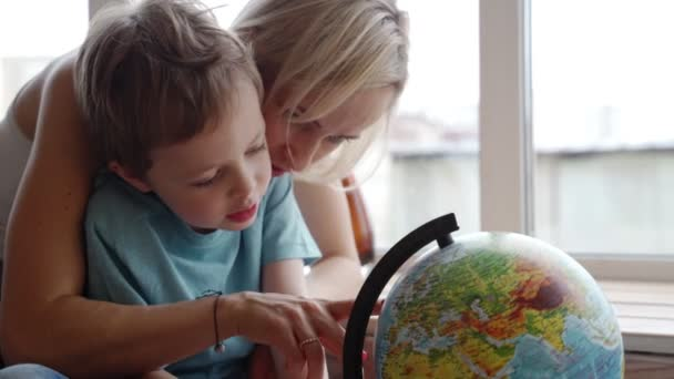 Atraktivní matkou kavkazského etnika používá glóbus Ukázat svého mladého syna, země světa.