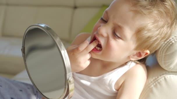 egy kis fiú, szőke haja tükörképe a száját megmutatni, ahol elvesztette az egyik Babys fogak