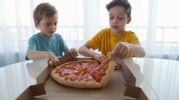 Two little caucasian boys eating pizza at home. Day light