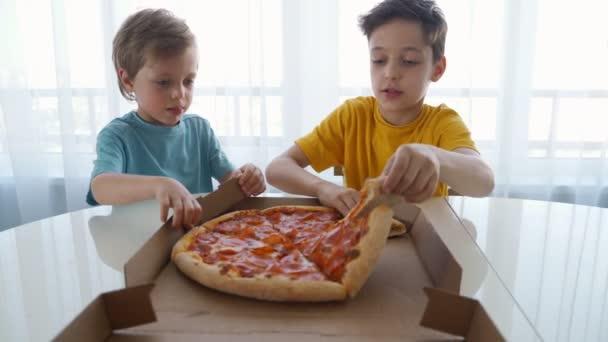 Két kis kaukázusi fiúk étkezési pizzát otthon. Nappali fény