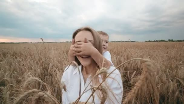 Young mother and child son lie in a wheat field hugging having fun together beautiful woman with little cute boy.