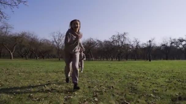 Anya egy gyerekkel játszik a parkban felzárkózás, rohangálás egymás körül, és szórakozás, a gyermek nem tudja elkapni az anya kacsák és ravaszság