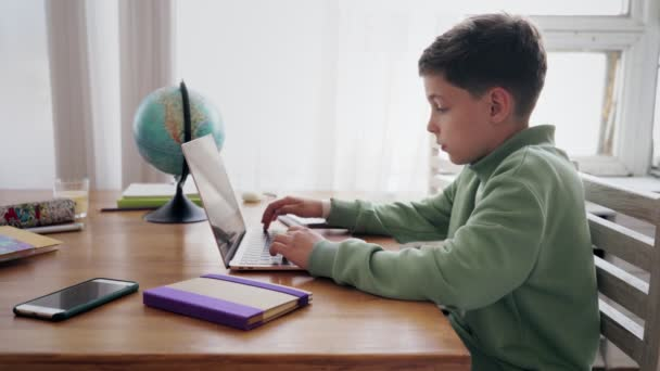 Vissza az iskolába, Online tanulás, távoktatás, oktatás otthon, technológia gyerekeknek. Kaukázusi fiú gépel egy laptopon