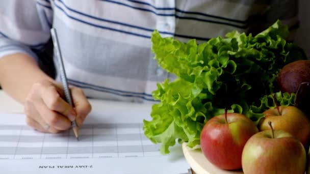 Woman writing diet plan on table full of fruits and vegetables
