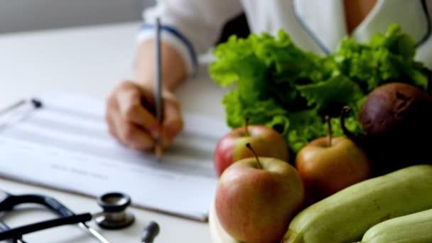 Výživu žena psaní dietní plán na stůl plný ovoce a zeleniny