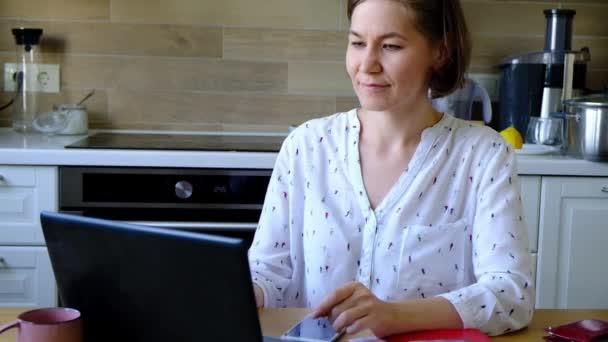 fröhliche und fröhliche Frau blickt in der Küche auf ihr Notizbuch.