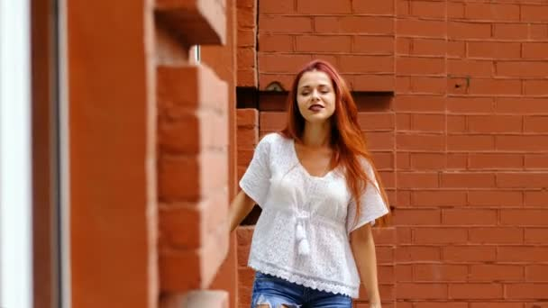 Portrait of sexy woman with long red hair, in the city. Fashion.