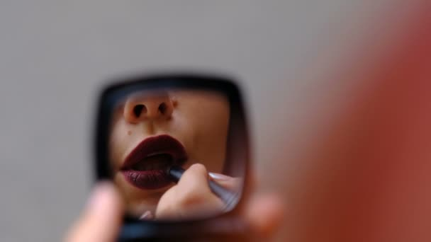 Woman looking in the mirror and putting on lipstick, close up