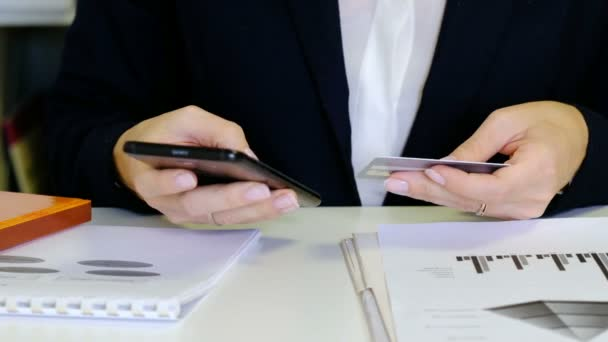 Online vásárlás koncepció. Nő hitelkártya és smartphone, közelről.