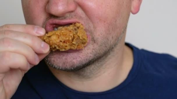 Fiatal ember eszik a csirke szárny. Fast food koncepció. Közelről