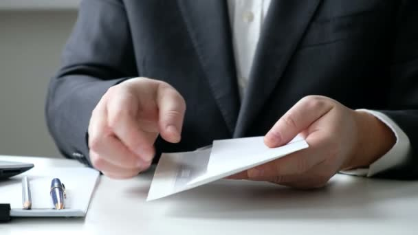 A man giving bribe money in a white envelope to another businessman in a corruption scam