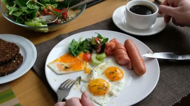 Člověk pojídá snídani. Nůž a vidličku v ruce. Snídaně s opečeným vejcem, klobásou, salátem a toast.