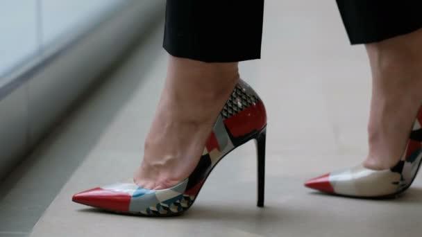 Žena v botách s moderním tiskem na vysokých podpatcích, zblízka
