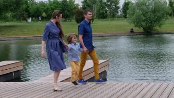 glückliches Familienkonzept: Mutter, Vater und kleiner Junge spazieren am Fluss entlang und haben Spaß