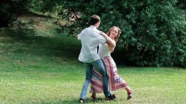 Happy young loving couple dancing waltz in the park, summer outdoors