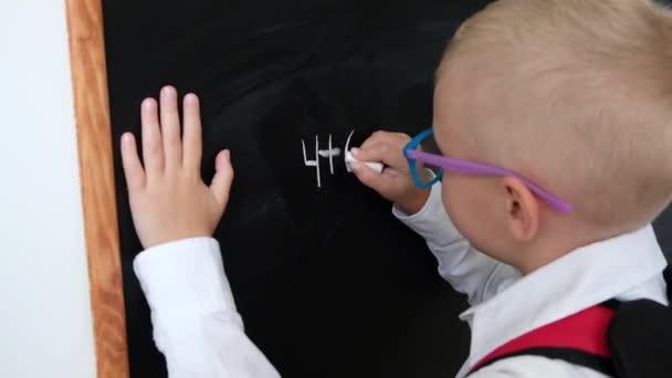 Netter kleiner Junge, der auf eine Tafel schreibt. Kind aus der Grundschule mit Tasche. Bildungskonzept. Zurück zur Schule.