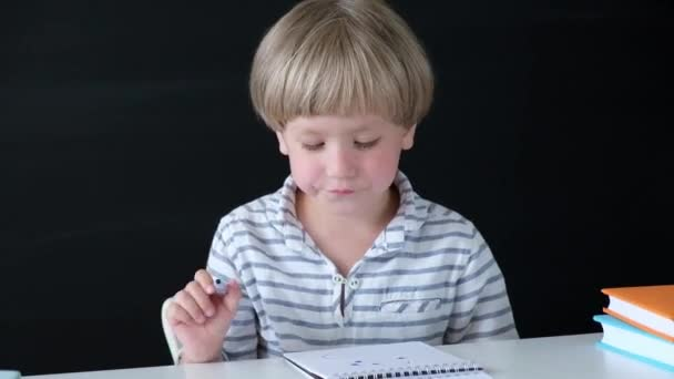 Cute little boy drawing at the table. Child from elementary school. Education concept. Back to school.