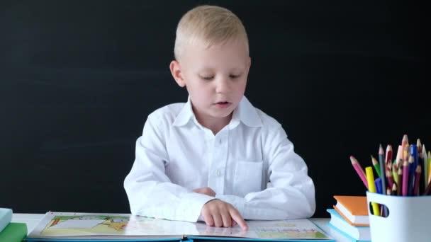 Aranyos kisfiú ül az asztalnál, és olvasás. Gyermek az elemi iskolából. Oktatási koncepció. Vissza az iskolába.