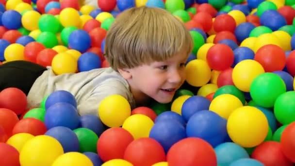 Cute toddler boy, child, playing in colorful balls in children playground, indoors
