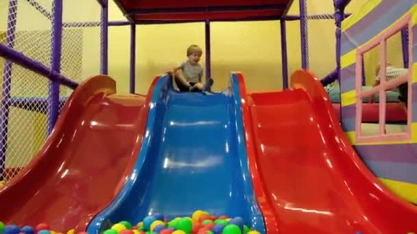 Cute toddler boy, child, riding on the hill in colorful balls in children playground, indoors
