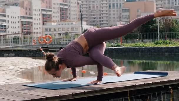 Young woman doing yoga exercises with city on background. eka pada kaundiniasana