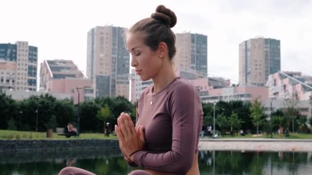 Mladá žena sedí v jóga a má město na pozadí. Koncepce relaxace a svobody.