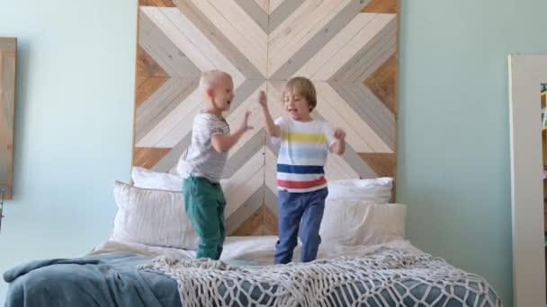Aufgeregte Kinder springen auf das Bett. Glückliche Kinder am Morgen.