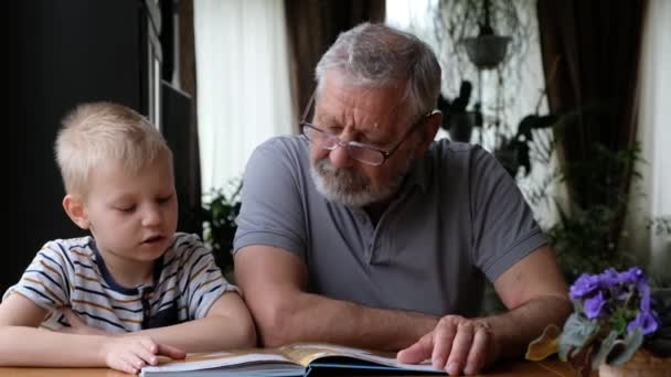 Grandfather senior man reading a book with his grandson