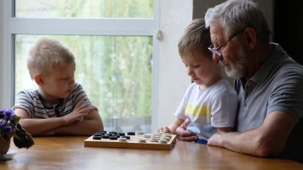 Little boys children play checkers with grandfather at home, senior positive man