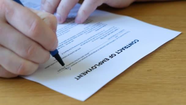 Ein unkenntlich gemachter Mann füllt einen Arbeitsvertrag aus. Nahaufnahme