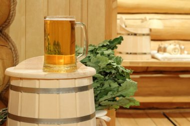 A mug of  light beer in the sauna on the background of bath accessories.