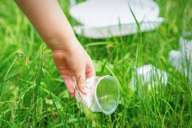 Little girl cleans plastic utensils on the green grass in the park