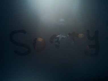 Word sorry on the mirrior, Abstract blurred Love heart symbol drawing on foggy window