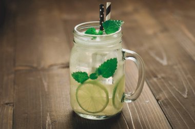 Cold Mojito Cocktail with Ice, Lemon and Mint Leaves in Mason Jar on Rustic Dark Wooden Background as Summer Concept