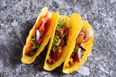 Three Pork Tacos in Shells on Stone Background