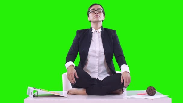 Portrait of young business woman in the office. She sat on the Desk in the Lotus position and meditating in a business suit. Green background.