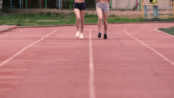 3fa7596c65 Dos chicas deportivas slim en pantalones cortos corriendo por el estadio en  cámara lenta– metraje de stock